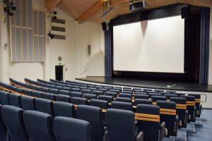 En sal där finns bänkrader och en scen med en filmduk.