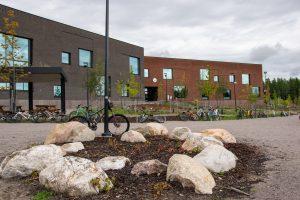 En skolbyggnad. Framför byggnaden finns gåden och barnens cyklar.