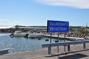 En skylt där det står Kalkstrand. Båtar i hamnen bakom skylten.