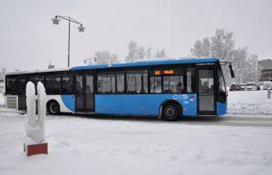 En buss som kör på gatan och snörik landskap.