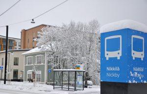 En skylt med text Nickby, gatan och snörik landskap.