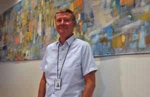 Kommundirektör Mikael Grannas står framför en målning.