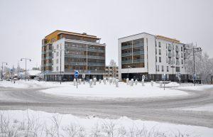 En rondell och flera höghus bakom rondellen under vintertid.