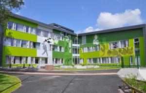 En stor byggnad med grön fasad.