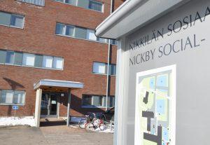 En skylt där det står Nickby social....En byggnad bakom skylten.