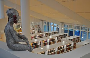 En staty sitter på ett räcke och tittar ner mot bokhyllor.