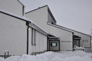 En vit byggnad och snö kring byggnaden.