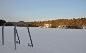 En sjö under vintertid. Snö och en brygga.
