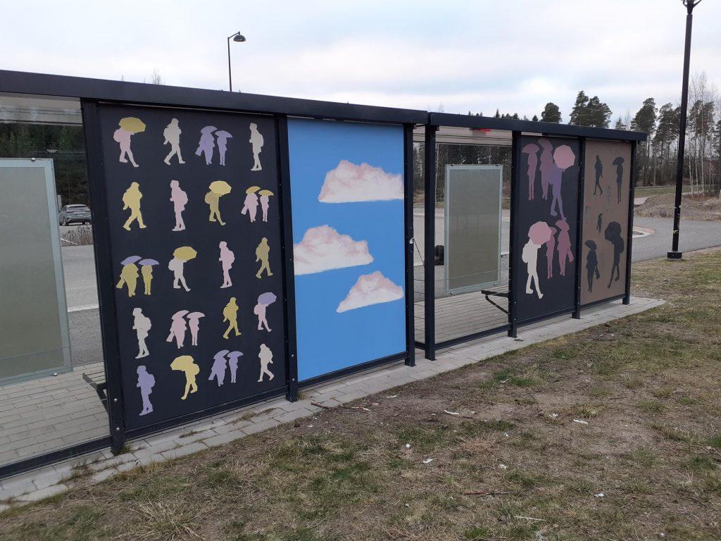 Bussipysäkki kuvattuna takaa, vanerilevyseinissä Sipoonlahden koulun oppilaiden tekemiä taideteoksia. Ihmisiä sateenvarjon kanssa ja sinisellä taustalla pilviä.