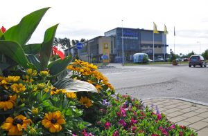 En blomsterplantering och bakom den syns gatan och Söderkulla centrum.