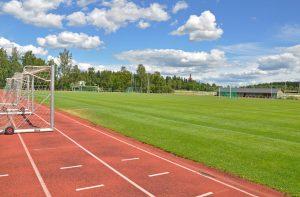 En idrottsplan där finns löpbanor, grasplan och fotboll mål.
