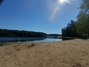 Sandy beach of Pilvijärvi with swimming pier in the background.