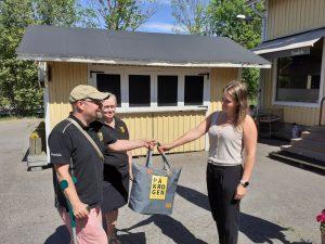 På Krogen Restaurant's owner couple hands a picnic bag to Municipality of Sipoo Business coordinator Anne Peltonen.