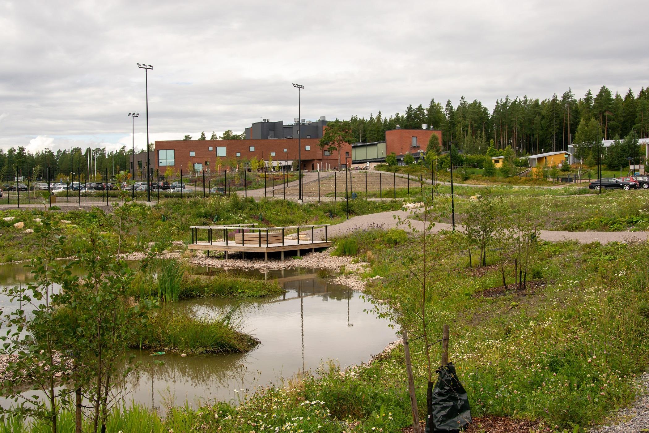 Miilin aluetta. Puistomaista aluetta, jonka taustalla näkyy rakennuksia ja pysäköintialuetta.