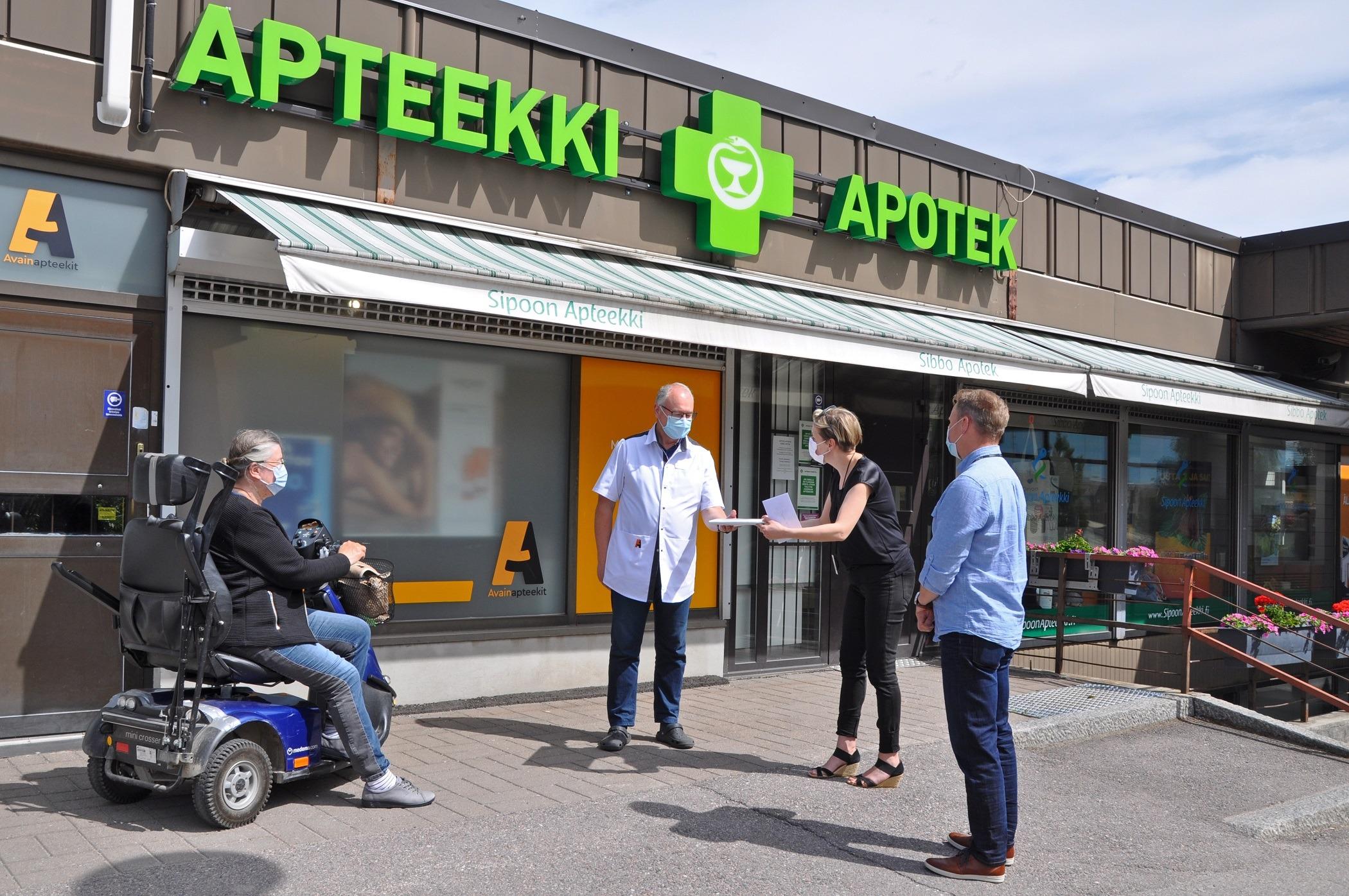 Jukka Suhonen, Tuula Räikkönen och näringschef Elina Duréault uppvaktar apotekaren Hans Fock framför Sibbo Apotek.